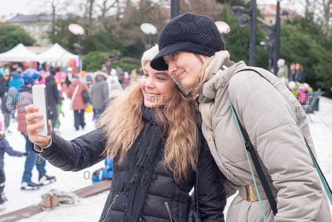 Smiling girls taking a selfie at an ice rink