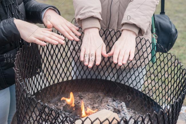Girls warming their hands over a fire outdoors