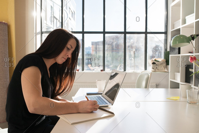 Woman writing notes while using a laptop in a casual office