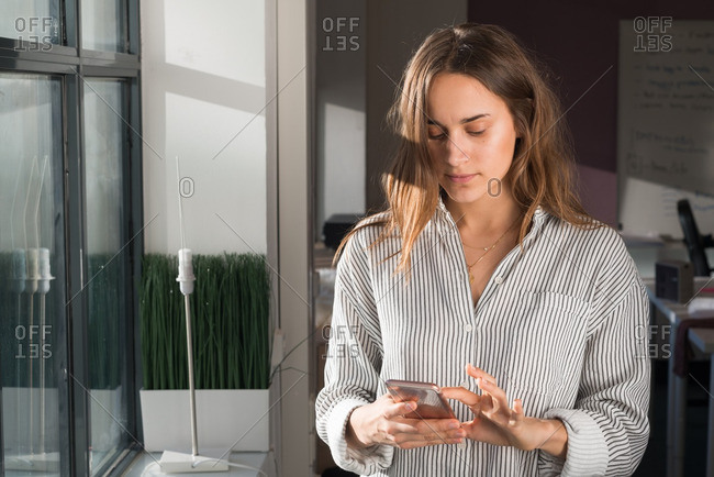 Portrait of a brunette woman texting on her phone in a casual office