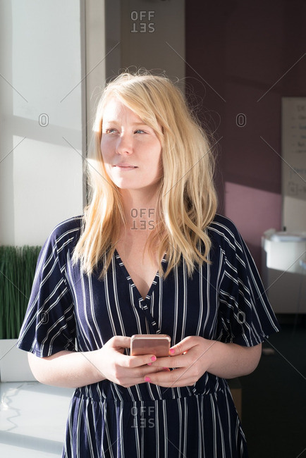Blonde woman holding a phone in a casual office
