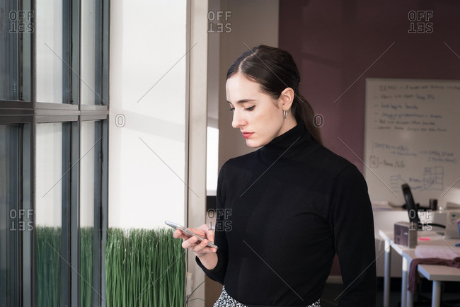 Brunette woman texting on her phone in a casual office