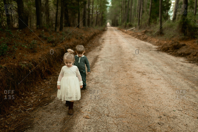 Two toddlers with blonde hair walking down a dirt road