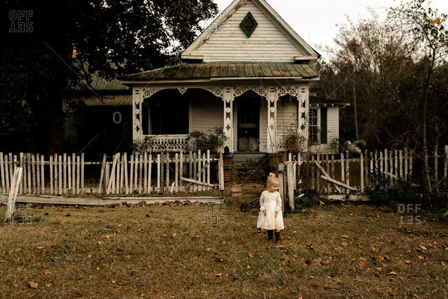 Toddler girl with blonde hair in front of an old country house