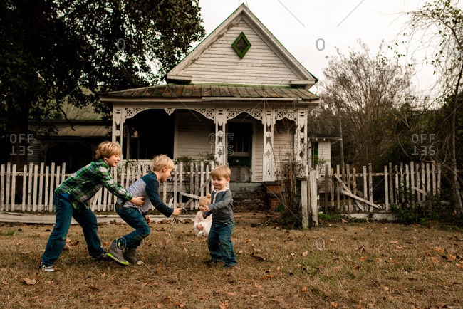 Siblings with blonde hair in front of an old country house