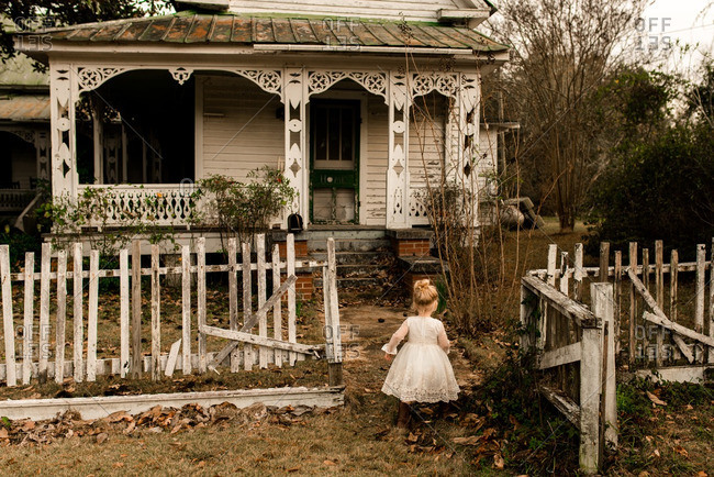 Little girl with blonde hair in front of an old country house