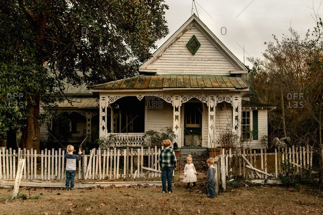 Siblings playing in front of an old country house