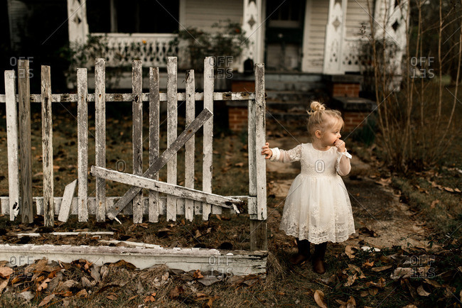 Toddler girl in front of an old country house