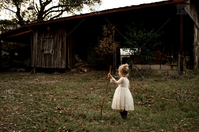 Little girl with blonde hair in front of an old barn