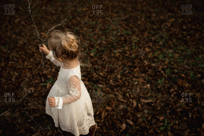 Little girl with blonde hair walking with a stick