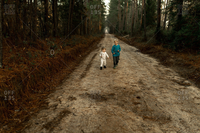 Two brothers walking down a dirt road