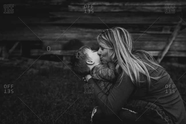 Mother kissing toddler boy in black and white