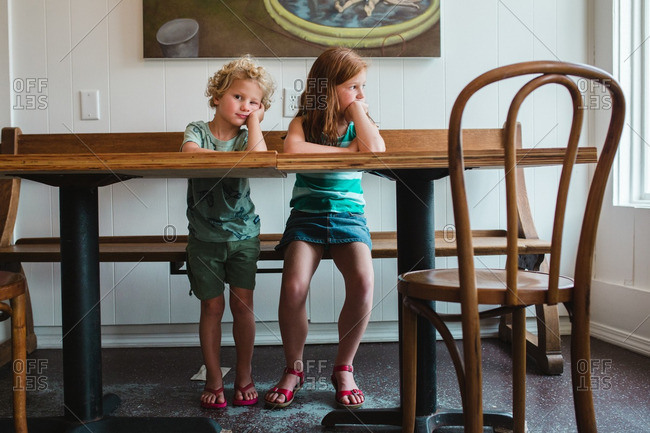 Siblings sitting at a table looking bored