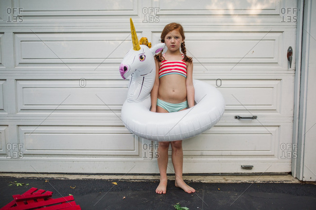 Little girl standing with a unicorn inflatable
