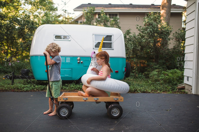Siblings playing with a wagon and a pool inflatable
