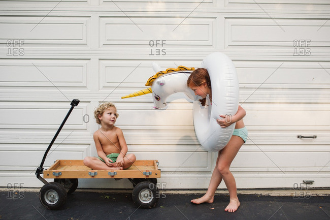 Siblings playing by a garage door with a wagon and a pool inflatable