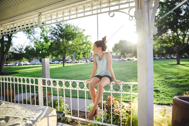 Lonely girl sitting on railing of gazebo in a park