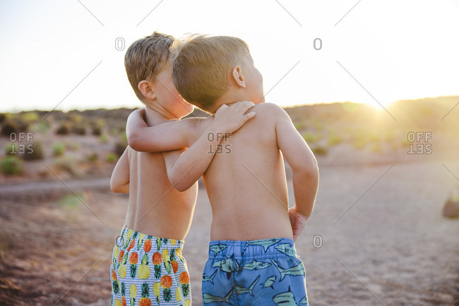 Best friends hugging on the beach at sunset