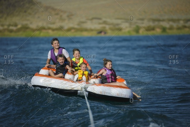 Kids tubing behind a boat on a scenic lake