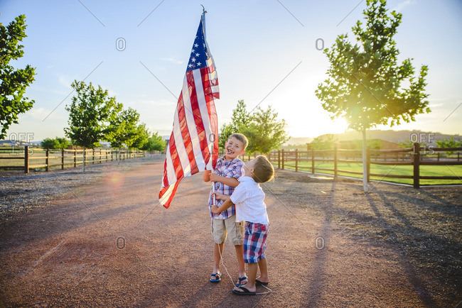 Two boys holding an American flag at sundown