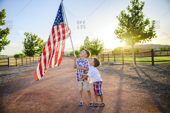 Two boys holding an American flag at sunset