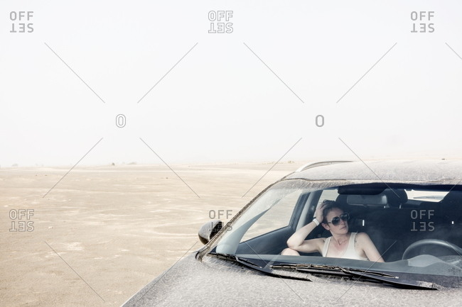 Woman sitting in a car in the island's desert