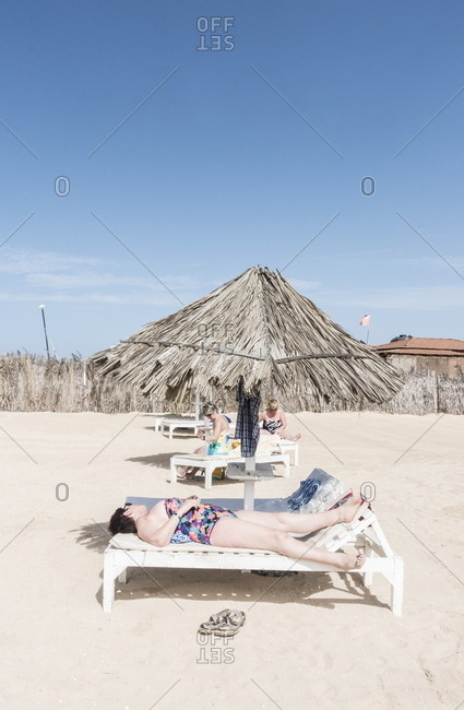 Boa Vista, Cape Verde - January 3, 2017: People relaxing in lounge chairs on the beach
