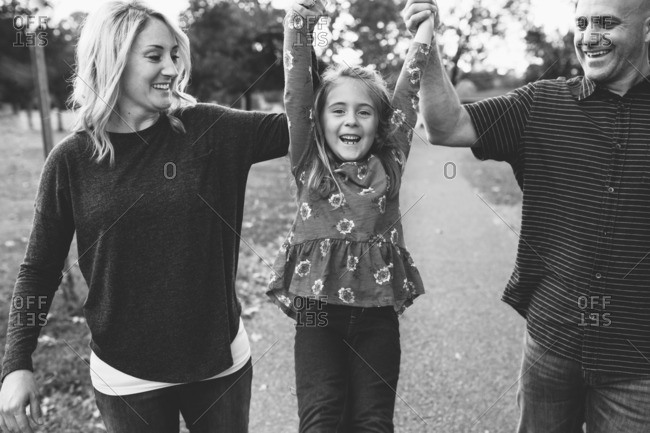 Parents hold daughters hands as she jumps