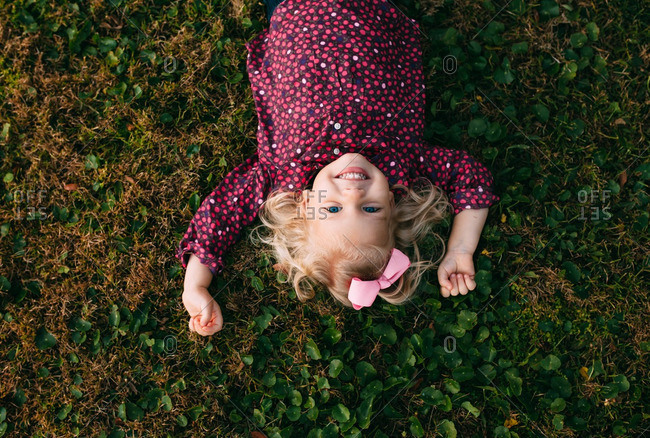 Overhead view of toddler girl lying in grass