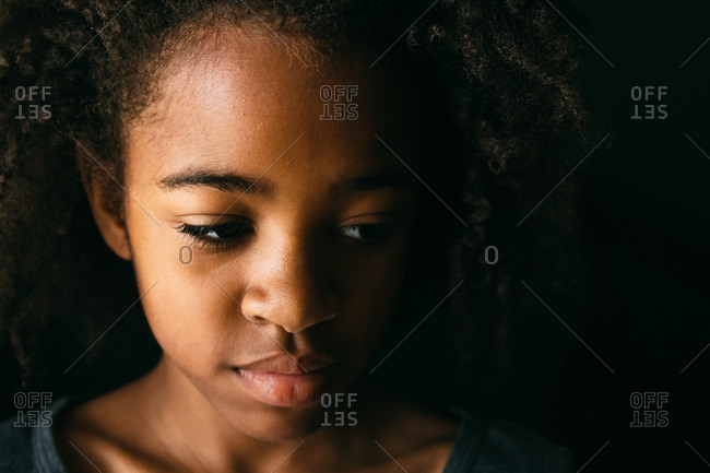 Close-up portrait of a beautiful young girl looking down