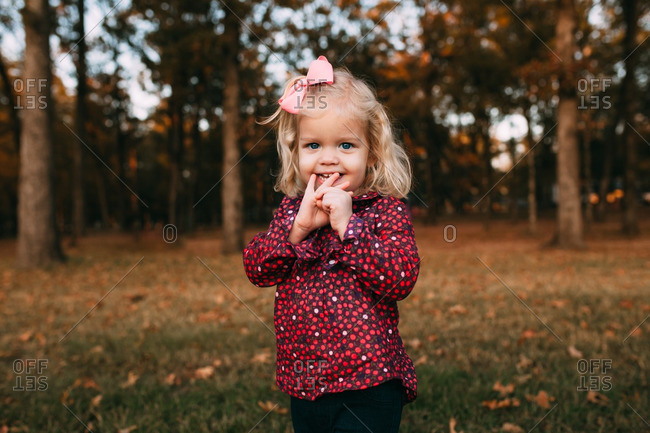 Cute toddler girl standing in the woods in autumn