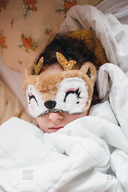 Little girl in a deer sleep mask bundled under covers