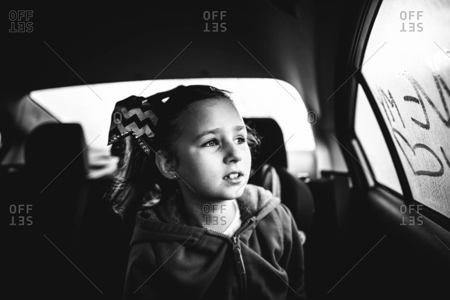 Little girl looking out the back seat window of a car
