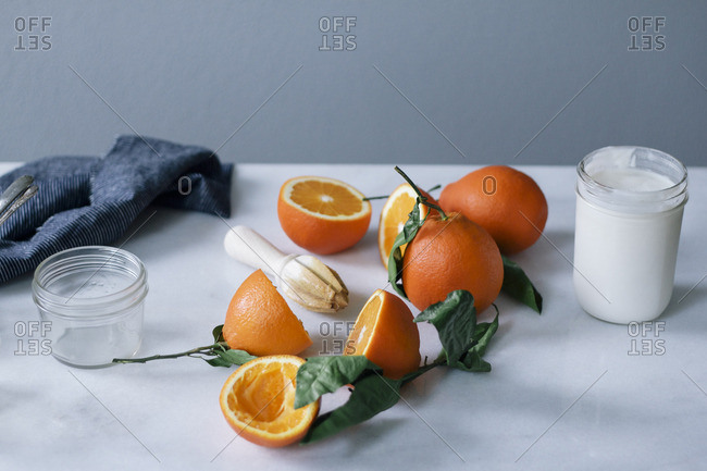 Oranges, citrus reamer and jar of cream on a counter