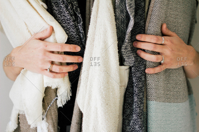 Woman's hands wrapped around a bundle of neutral colored scarves