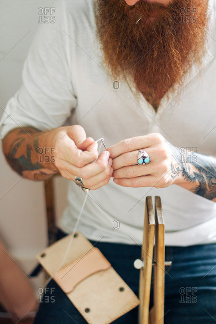 Man with a red beard threading a needle to string an instrument