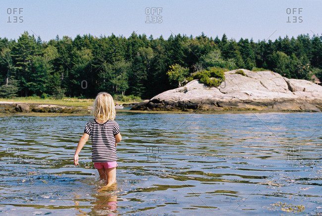 Little girl wading in a shallow lake