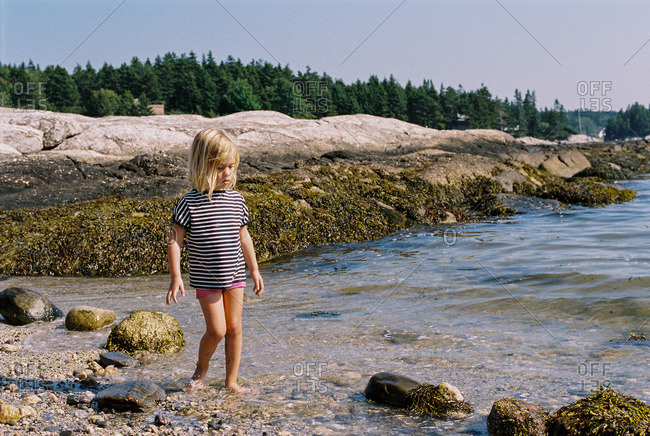 Little girl walking on a pebble beach at a lakeshore