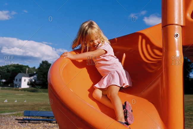 Girl on an orange spiral slide at a playground