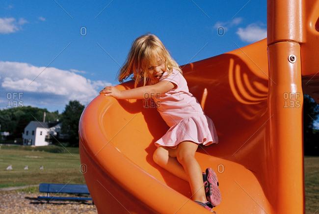 Girl on an orange spiral slide at a playground