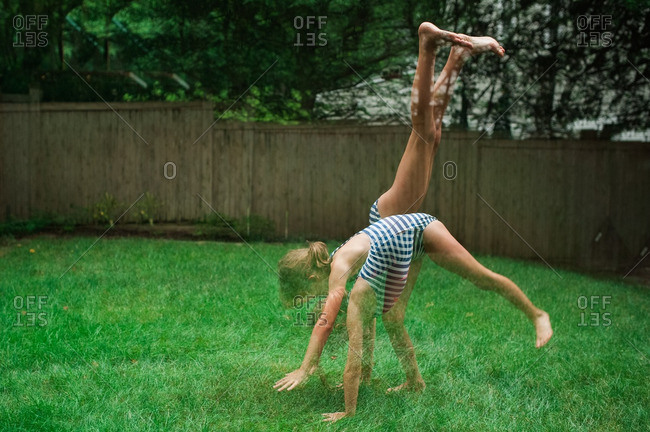 Girl in a swimsuit doing a handstand in a backyard