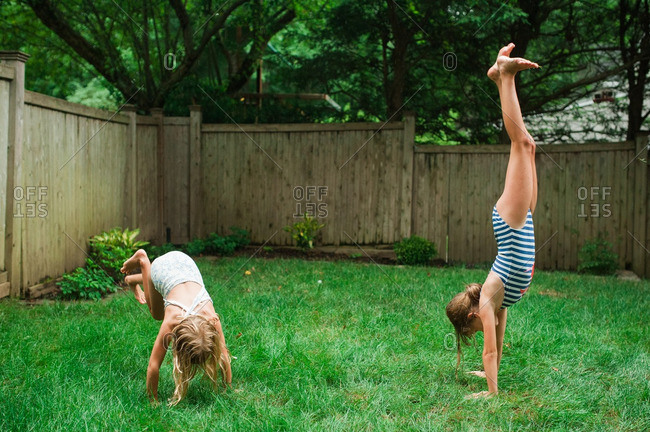 Two sisters in bathing suits doing cartwheels in a backyard