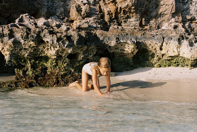 Little girl playing in clear water on a beach