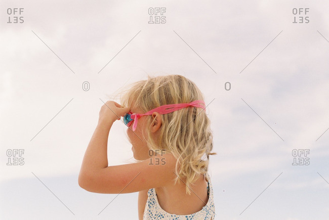 Little girl in a swimsuit adjusting her goggles