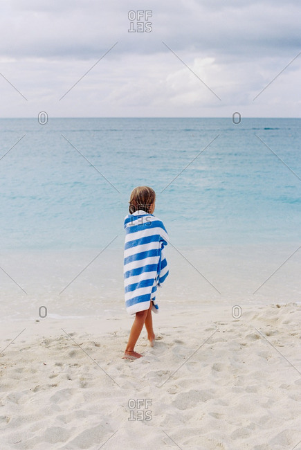 Girl wrapped in a striped towel walking on a beach