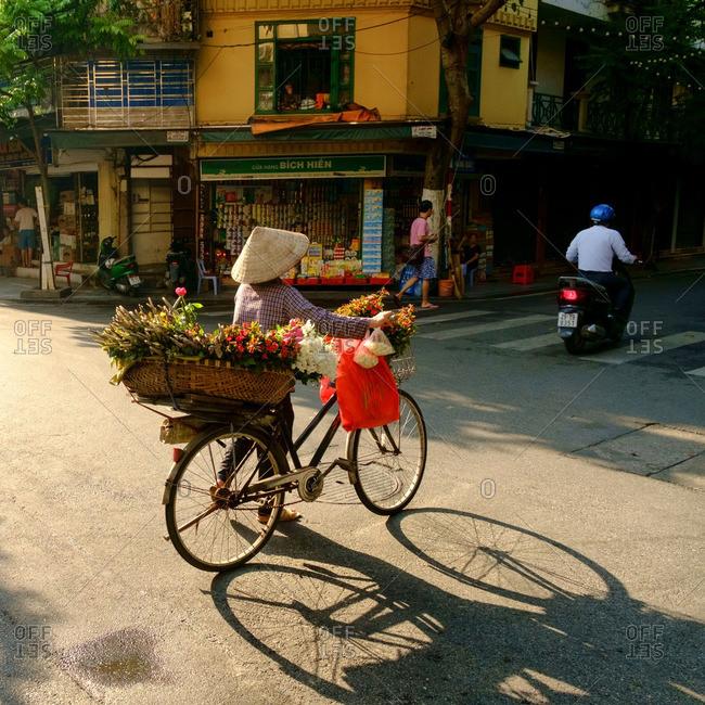 Hanoi, Vietnam - 7/9/16: Flower vendor crossing an intersection