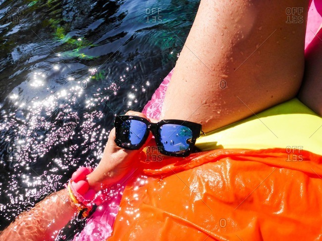 Woman holding pair of sunglasses while sitting in water