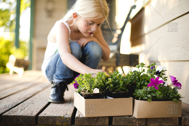 Young girl with plants on front porch