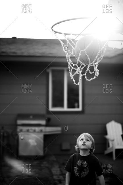 Boy watching basketball go into net in backyard