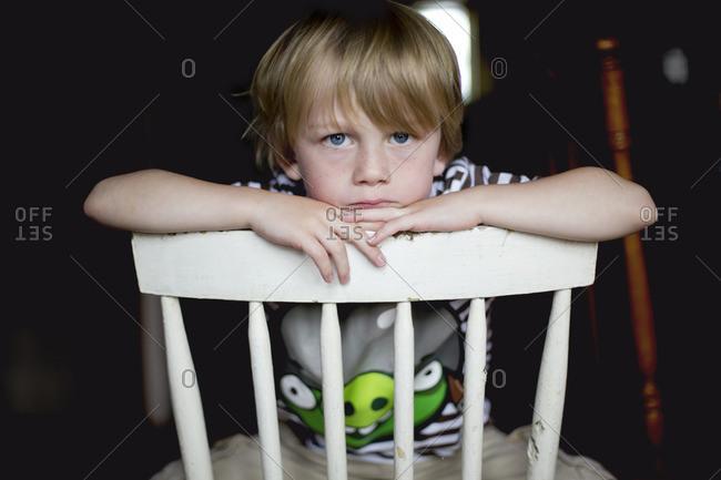 Grumpy young boy sitting backwards on chair